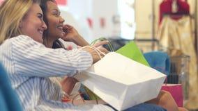 Gelukkige jonge vrouwen die het winkelen zakken onderzoeken stock videobeelden