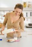 Gelukkige jonge vrouwen gietende melk in glas Stock Foto's