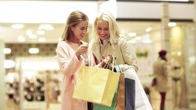 Gelukkige jonge vrouwen met het winkelen zakken in wandelgalerij stock videobeelden