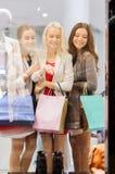 Gelukkige jonge vrouwen met het winkelen zakken in wandelgalerij Royalty-vrije Stock Foto's