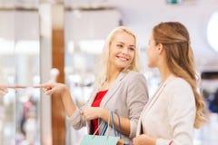 Gelukkige jonge vrouwen met het winkelen zakken in wandelgalerij Stock Afbeelding