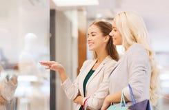 Gelukkige jonge vrouwen met het winkelen zakken in wandelgalerij Stock Fotografie
