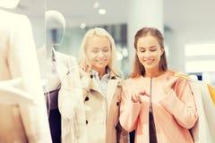 Gelukkige jonge vrouwen met het winkelen zakken in wandelgalerij Stock Foto's
