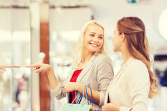 Gelukkige jonge vrouwen met het winkelen zakken in wandelgalerij Royalty-vrije Stock Afbeeldingen