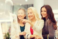 Gelukkige jonge vrouwen met het winkelen zakken in wandelgalerij Royalty-vrije Stock Afbeelding