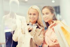 Gelukkige jonge vrouwen met het winkelen zakken in wandelgalerij Stock Foto