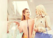 Gelukkige jonge vrouwen met het winkelen zakken in wandelgalerij Royalty-vrije Stock Foto