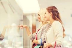 Gelukkige jonge vrouwen met het winkelen zakken in wandelgalerij Stock Afbeeldingen