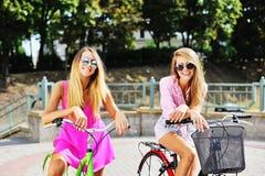 Gelukkige jonge vrouwen op fietsen in zomer Royalty-vrije Stock Fotografie