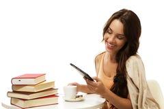 Gelukkige jonge vrouwenlezing ebook dichtbij boeken stock afbeeldingen