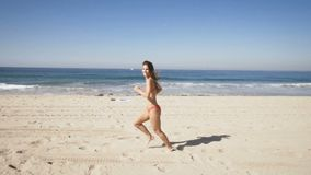 Gelukkige jonge vrouwenlooppas bij het strand van Manhattan in Californië Jonge volwassenen stock videobeelden
