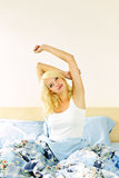Gelukkige jonge vrouwenontwaken in bed royalty-vrije stock fotografie