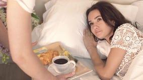 Gelukkige jonge vrouwenontwaken wanneer haar echtgenoot haar koffie in bed brengt stock videobeelden