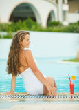 Gelukkige jonge vrouwenzitting bij pool met cocktail Royalty-vrije Stock Foto