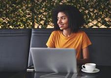 Gelukkige jonge vrouwenzitting in koffie met laptop op lijst stock fotografie