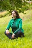 Gelukkige jonge vrouwenzitting op gras royalty-vrije stock afbeeldingen