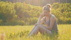 Gelukkige jonge vrouwenzitting op groen gazon en het spreken op de telefoon of smartphone stock video