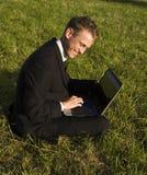 Gelukkige jonge zakenman die in het park werkt royalty-vrije stock foto