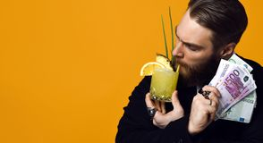 Gelukkige jonge zakenman die met glas van cocktail in formele kleding bos van geldbankbiljetten houden royalty-vrije stock foto