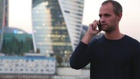 Gelukkige jonge zakenman die op celtelefoon dichtbij commercieel centrum spreken stock video