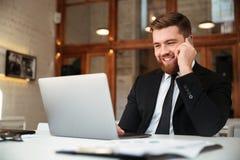 Gelukkige jonge zakenman in zwart kostuum die op mobiele telefoon, l spreken royalty-vrije stock afbeelding