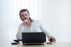 Gelukkige jonge zakenmanzitting bij zijn bureau met laptop Stock Afbeeldingen