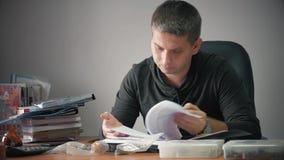 Gelukkige jonge zakenmanzitting in bureau met handelspapieren op lijst Het knappe mens werken, die bij bureau in huis schrijven stock video