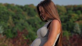 Gelukkige jonge zwangere vrouw die bij de camera glimlachen stock videobeelden