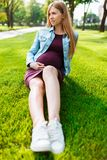 Gelukkige jonge zwangere vrouwenzitting in het park op het gazon royalty-vrije stock afbeeldingen