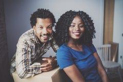 Gelukkige jonge zwarte Afrikaanse paar bewegende dozen in nieuwe flat samen en makend het mooi leven Vrolijke familie Stock Fotografie