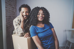 Gelukkige jonge zwarte Afrikaanse paar bewegende dozen in nieuwe flat samen en makend het mooi leven Vrolijke familie Royalty-vrije Stock Foto