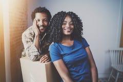 Gelukkige jonge zwarte Afrikaanse paar bewegende dozen in nieuwe flat samen en makend het mooi leven Vrolijke familie Royalty-vrije Stock Foto's