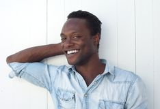 Gelukkige jonge zwarte mens die tegen witte achtergrond in openlucht glimlachen Royalty-vrije Stock Afbeelding