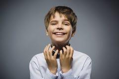 Gelukkige jongen Close-upportret van het knappe tiener pleiten of het beging op grijze achtergrond stock afbeeldingen