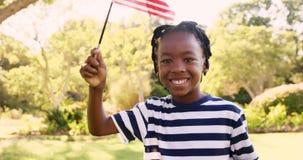 Gelukkige jongen die Amerikaanse Vlag golven bij park stock video