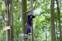 Gelukkige jongen die in avonturenpark beklimmen Stock Foto