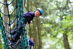 Gelukkige jongen die in avonturenpark beklimmen Stock Fotografie