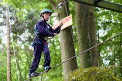 Gelukkige jongen die in avonturenpark beklimmen Stock Foto's