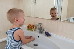 Gelukkige jongen die bad in keukengootsteen nemen Kind het spelen met schuim en zeepbels in zonnige badkamers met venster Weinig  Royalty-vrije Stock Foto