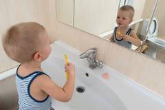 Gelukkige jongen die bad in keukengootsteen nemen Kind het spelen met schuim en zeepbels in zonnige badkamers met venster Weinig  Stock Afbeeldingen
