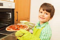 Gelukkige jongen die eigengemaakte pizza in de oven zetten royalty-vrije stock foto's