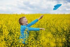Gelukkige jongen die en blauw document vliegtuig op heldere zon leunen werpen Royalty-vrije Stock Fotografie