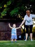 Gelukkige jongen die grappige gezichten en uitdrukkingen maken terwijl het lopen met zijn grootmoeder Stock Foto's