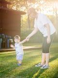 Gelukkige jongen die grappige gezichten en uitdrukkingen maken terwijl het lopen met zijn grootmoeder Stock Afbeeldingen