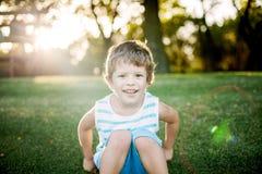 Gelukkige jongen die grappige gezichten en uitdrukkingen op groen gras maken stock afbeeldingen