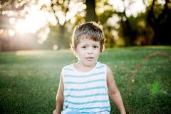 Gelukkige jongen die grappige gezichten en uitdrukkingen op groen gras maken royalty-vrije stock foto's