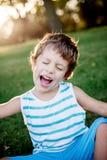 Gelukkige jongen die grappige gezichten en uitdrukkingen op groen gras maken stock fotografie