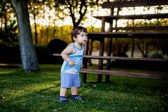 Gelukkige jongen die grappige gezichten en uitdrukkingen op groen gras maken stock afbeelding