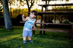 Gelukkige jongen die grappige gezichten en uitdrukkingen op groen gras maken royalty-vrije stock fotografie