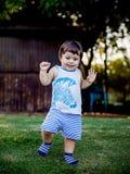 Gelukkige jongen die grappige gezichten en uitdrukkingen op groen gras maken stock foto